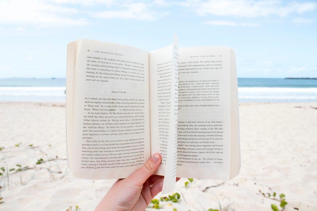 海辺の砂浜で本を広げている画像